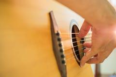 弹声学吉他的人的手 免版税库存图片
