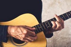 弹声学吉他的人 免版税库存照片