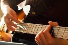 弹声学吉他的妇女的手 免版税库存图片