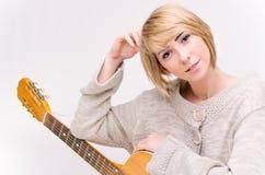弹声学吉他的灰色毛线衣的年轻美丽的微笑的白肤金发的夫人 库存图片