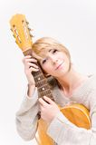 弹声学吉他的灰色毛线衣的年轻美丽的微笑的白肤金发的夫人 库存照片