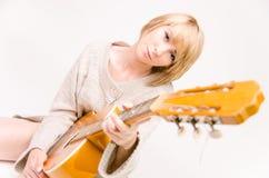 弹声学吉他的灰色毛线衣的年轻美丽的微笑的白肤金发的夫人 免版税库存图片