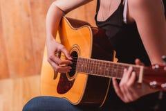弹声学吉他,关闭的妇女的手  库存照片