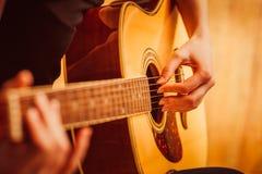 弹声学吉他,关闭的妇女的手  免版税库存图片