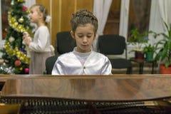 弹大平台钢琴的小女孩 一件美丽的礼服的一个女孩在一架棕色大平台钢琴使用 免版税图库摄影