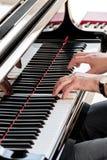 弹大平台钢琴和接触它的钥匙的音乐家或作曲家 库存图片