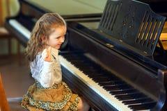 弹大平台钢琴的逗人喜爱的小女孩在音乐学院 库存图片