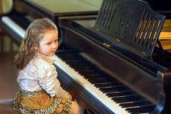 弹大平台钢琴的逗人喜爱的小女孩在音乐学院 免版税库存照片
