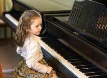 弹大平台钢琴的逗人喜爱的小女孩在音乐学院 图库摄影