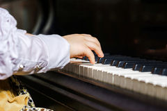 弹大平台钢琴的逗人喜爱的小女孩在音乐学院 免版税库存图片