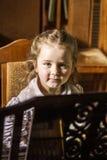 弹大平台钢琴的逗人喜爱的小女孩在音乐学院 免版税图库摄影