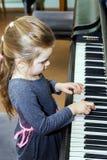 弹大平台钢琴的逗人喜爱的小女孩 免版税库存图片