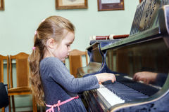 弹大平台钢琴的逗人喜爱的小女孩 库存图片