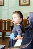 弹大平台钢琴的逗人喜爱的小女孩 免版税库存照片