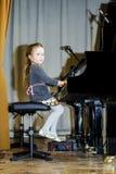 弹大平台钢琴的逗人喜爱的小女孩 免版税图库摄影
