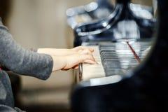 弹大平台钢琴的逗人喜爱的小女孩 图库摄影