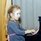 弹大平台钢琴的逗人喜爱的小女孩 库存照片