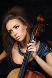 弹大提琴的美丽的女性音乐家 免版税图库摄影