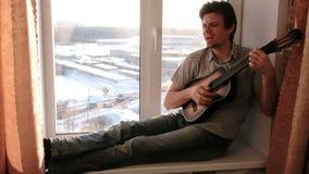 弹奏一个乐器 人弹坐在窗台的吉他 影视素材