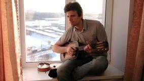 弹奏一个乐器 人弹坐在窗台的吉他 股票录像