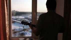 弹奏一个乐器 供以人员弹吉他的` s剪影在窗台附近 股票录像