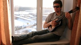 弹奏一个乐器 太阳镜的人弹吉他和唱歌坐在窗台 影视素材