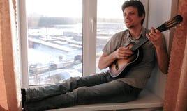 弹奏一个乐器 太阳镜的人弹吉他和唱歌坐在窗台 免版税库存照片