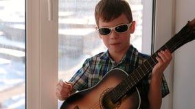 弹奏一个乐器 太阳镜的男孩弹吉他和唱歌坐窗台 影视素材