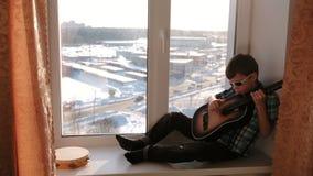 弹奏一个乐器 太阳镜的男孩弹吉他坐窗台 股票录像