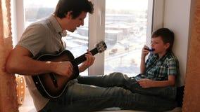弹奏一个乐器 爸爸弹吉他,并且儿子演奏坐在窗台的口琴 股票视频
