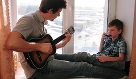 弹奏一个乐器 爸爸弹吉他,并且儿子演奏坐在窗台的口琴 免版税库存图片
