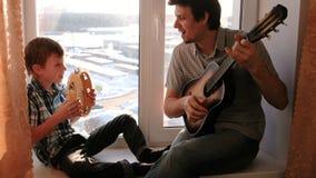 弹奏一个乐器 爸爸弹吉他,并且儿子演奏坐在窗台的小手鼓 股票视频