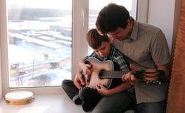 弹奏一个乐器 爸爸教他的儿子弹吉他,坐窗台 免版税库存照片