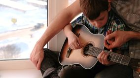 弹奏一个乐器 爸爸教他的儿子弹吉他,坐窗台 股票录像
