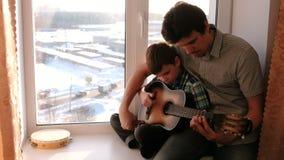 弹奏一个乐器 爸爸教他的儿子弹吉他,坐窗台 影视素材