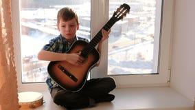 弹奏一个乐器 男孩弹吉他和唱歌坐窗台 影视素材