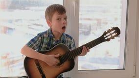 弹奏一个乐器 男孩弹吉他和唱歌坐窗台 股票录像