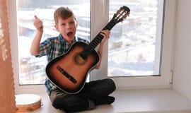 弹奏一个乐器 男孩弹吉他和唱歌坐窗台 免版税库存照片