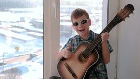 弹奏一个乐器 男孩弹吉他和唱歌坐窗台slomo 股票视频