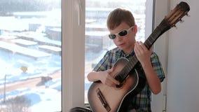弹奏一个乐器 男孩弹吉他和唱歌坐窗台slomo 影视素材