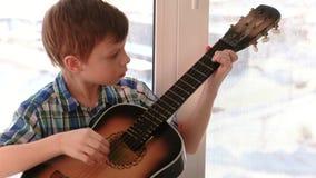 弹奏一个乐器 男孩弹吉他坐窗台 股票录像