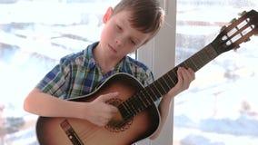 弹奏一个乐器 男孩弹吉他坐窗台slomo 股票录像