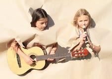 弹奏乐器的女孩通过孔 免版税库存图片