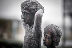 弹奏乐器的孩子雕象  免版税图库摄影