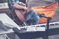 弹奏乐器的被集中的年轻障碍在演播室 免版税库存照片