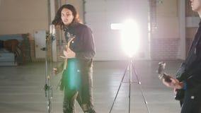 弹奏仪器的年轻人在明亮的屋子 有来离鼓手较近的吉他的一个独奏者 股票视频