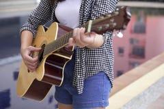 弹奏吉他仪器的特写镜头亚裔妇女由水池 库存照片