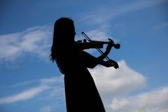 弹奏在剪影形状的亚裔妇女小提琴仪器与s 库存照片