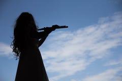 弹奏在剪影形状的亚裔妇女长笛仪器与sk 库存图片
