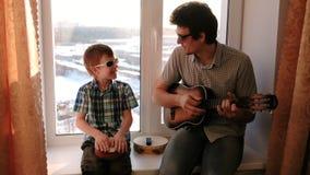 弹奏在太阳镜的一个乐器 爸爸弹吉他,并且儿子演奏坐在窗台的鼓 股票视频